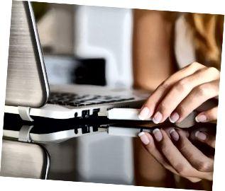 Kvinnahand som pluggar en pendrive hemma på en bärbar dator