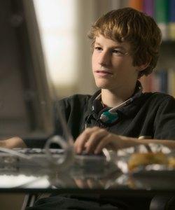 stile di vita ritratto di un maschio adolescente mentre si siede al suo computer e lavora