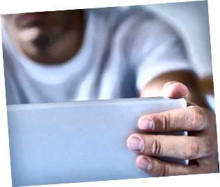 Primer plano de los dedos de un hombre abriendo una computadora portátil