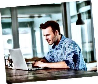 Junger Mann im Café, das auf Laptop tippt