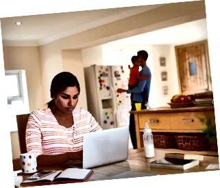 Familie in der Küche mit Mutter mit Laptop am Tisch