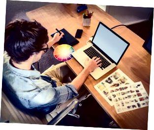 Glücklicher Designer, der an seinem Laptop arbeitet
