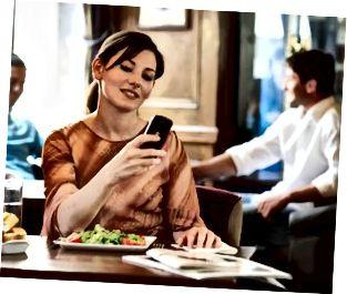 Donna seduta al tavolo nel bar, guardando il telefono cellulare, sorridente