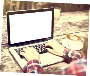 Mädchen mit einer Tasse Kaffee und einem leeren Laptop