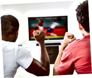 To mænd i stuen ser tv og jubler