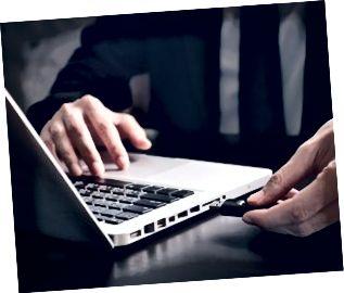 L'uomo d'affari che usando l'azionamento dell'istantaneo si collega al computer portatile