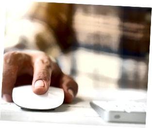 Lalaki kamay na may hawak na computer mouse gamit ang laptop keyboard sa background