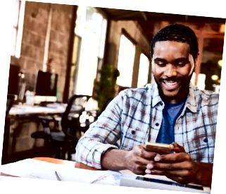 Designer sitter vid mötetabellen smsar på mobiltelefonen