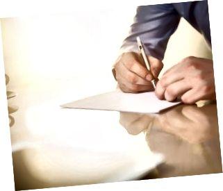 Las manos masculinas con un bolígrafo y la copa