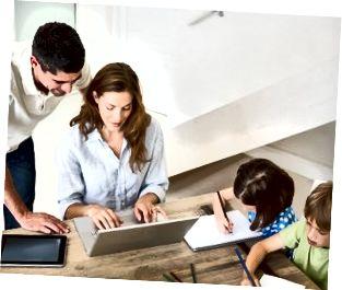 Eltern, die Laptop verwenden, während Kinder zu Hause färben