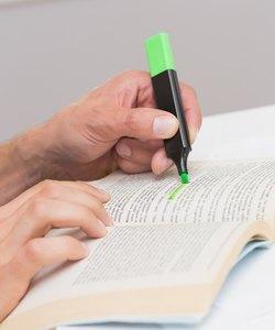 Manos resaltando texto en libro sobre la mesa