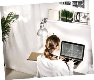 Tillbaka sikt av den mogna affärskvinnan som hemma arbetar med bärbara datorn.