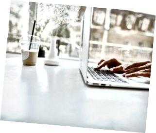 Händer som smsar på den bärbara tangentbordet på den vita tabellen
