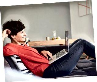 Gülümseyen kadın evde kanepede dizüstü bilgisayar kullanarak