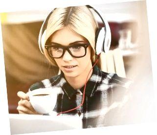 Den glada unga kvinnan vilar med teknologi