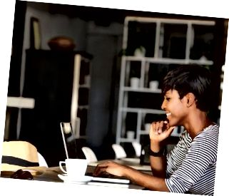 Ноутбукта жұмыс жасайтын африкалық американдық жас күлімсіреу