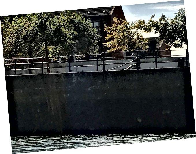Nehirdeki bir gemi için demirleme hatlarını çalıştıran bir adamı tasvir eden bir başka ilginç heykel