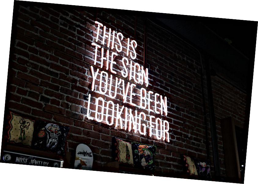 "Austin Chan tarafından Unsplash ""Bir mağazada bir tuğla duvara parlak neon"""