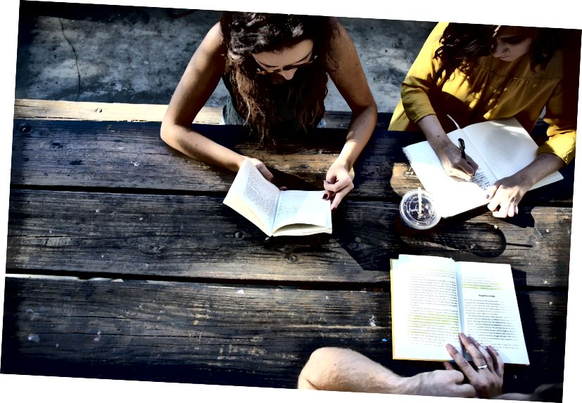 Ba người đọc và ghi chú tại một chiếc bàn gỗ cũ ngoài trời.
