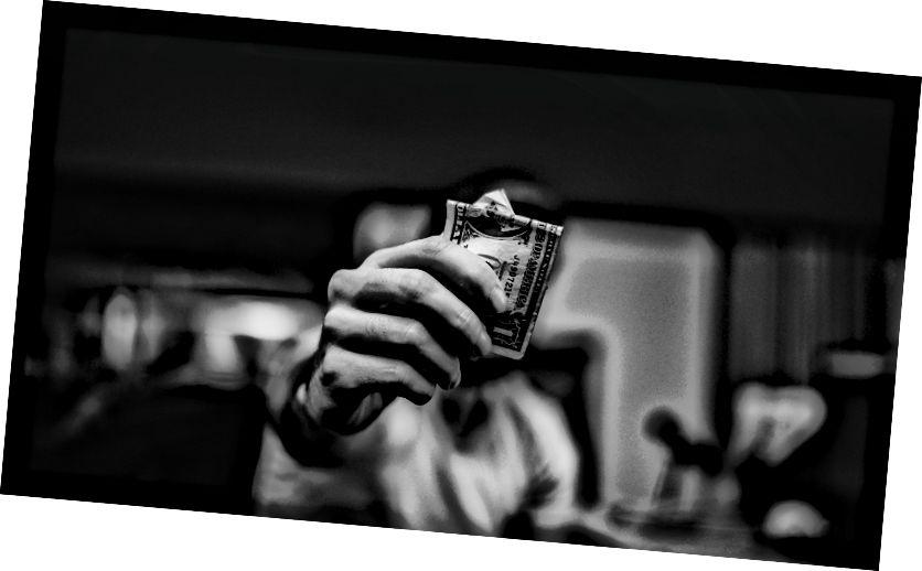 Người đàn ông nắm giữ 1 tờ tiền giấy đô la Mỹ của lucas Favre trên Bapt