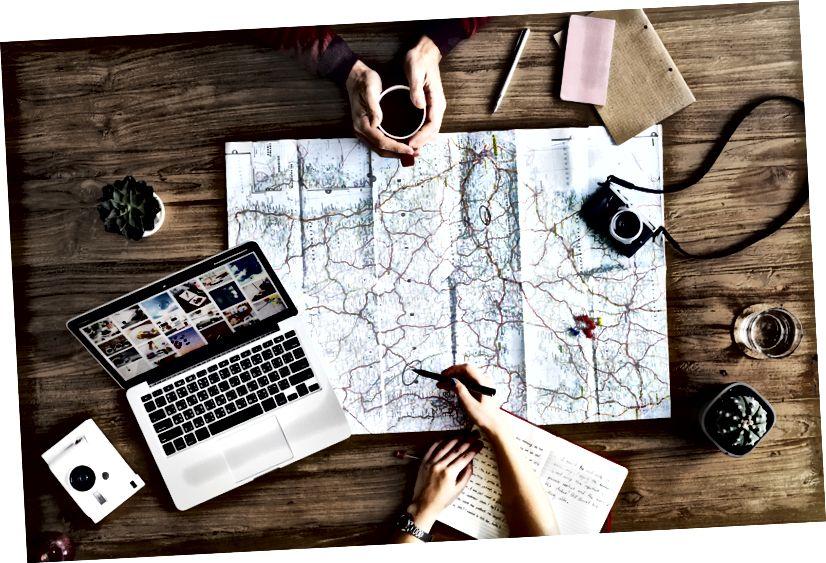 """""""Iki kişinin bir harita ve ahşap bir yüzey üzerinde bir dizüstü bilgisayar ile bir seyahat planlama havai bir çekim"""" tarafından rawpixel.com Unsplash"""