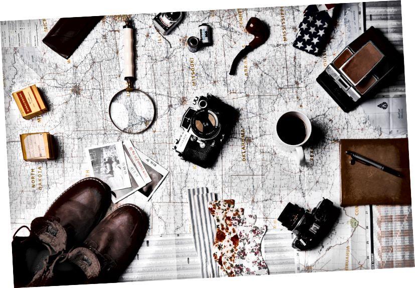 Một tấm phẳng của một chiếc kính lúp, một tách cà phê, máy ảnh, hình ảnh và các vật dụng du lịch khác nhau trên bản đồ, bởi ian dooley trên.