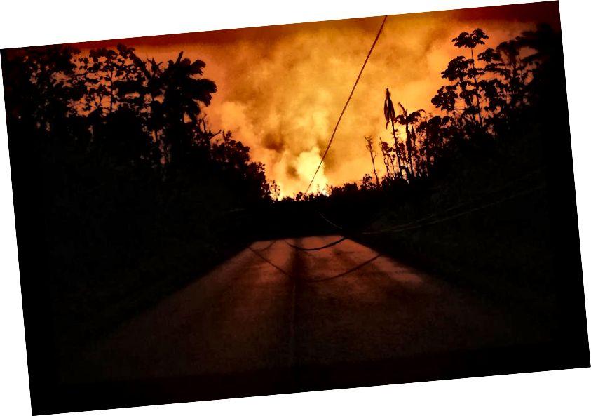 Dung nham từ khe nứt núi lửa Kīlauea chặn một con đường và chiếu sáng bầu trời đêm ở Leilani Estates, trên Đảo Lớn của Hawaii, vào ngày 25 tháng 5 năm 2018 tại Pāhoa, Hawaii. Các trận động đất nhỏ hơn và các đám tro lớn, cùng với sulfur dioxide phát ra, tiếp tục gây ra thảm họa cho đỉnh K summlauea và vùng rạn nứt phía đông thấp hơn. (Hình ảnh Mario Tama / Getty)