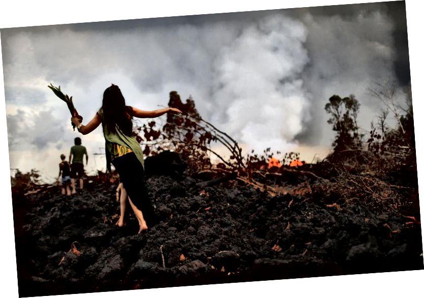 Geleneksel bir hula uygulayıcısı (L), 27 Mayıs 2018'de Hawaii'deki Pahoa'da Hawaii'nin Büyük Adasında bir Kīlauea yanardağ fissüründen soğutulmuş bir lav akışı üzerinde yürürken bir teklif taşıyor. Hawaii yanardağları ve ateş tanrıçası Madame Pele için bir törende teklifler bırakıldı. Hula, Hawaii'nin tarihini ve kültürünü izleyen tezahüratlar veya şarkılar eşliğinde Hawaii dans formudur. (Mario Tama / Getty Images)
