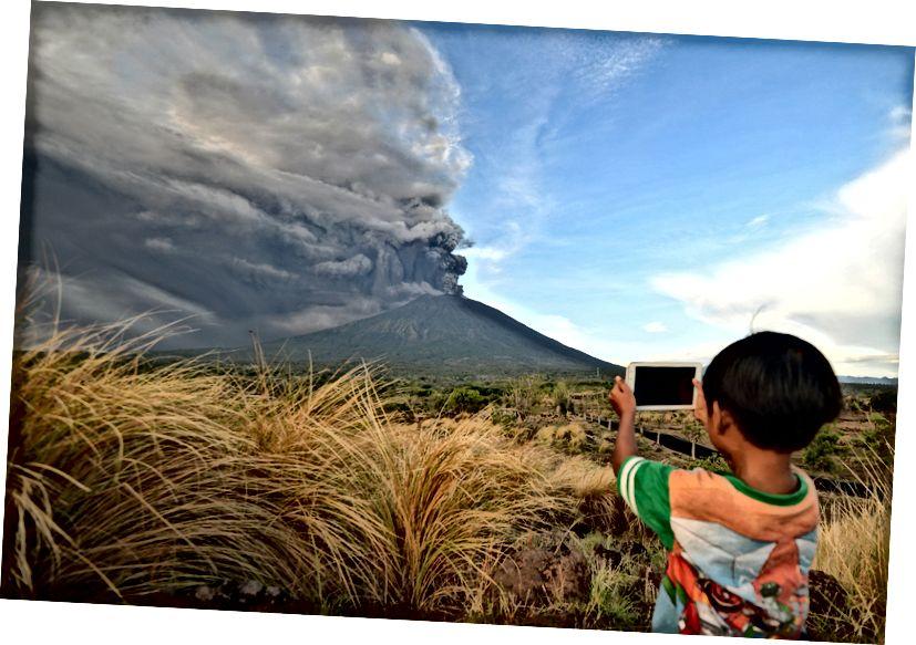 Un garçon prend des photos lors de l'éruption du mont Agung vu du sous-district de Kubu à Karangasem Regency sur l'île balnéaire d'Indonésie le 26 novembre 2017. Photo de Sonny Tumbelaka / AFP / Getty Images.