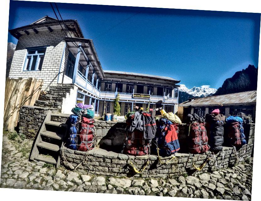 Timangi küla | Porteri kotid, taga lamades vägev Manaslu. Manaslu on 8163 meetri kõrgusel kaheksas kõrgeim mägi maailmas. ACT-l võib kohata 3 maailma kaheksast tuhandest kolmest. Annapurna, Dhaulagiri ja Manaslu