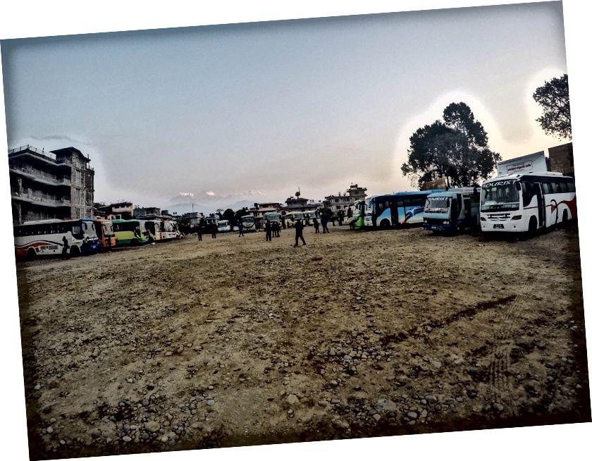 Keluar dari Nepal dengan naik bus ke kota Perbatasan India, Sunauli | Stasiun bus wisata dengan rentang Machapucchare dan Annapurna terlihat suram di langit yang dipenuhi kabut.