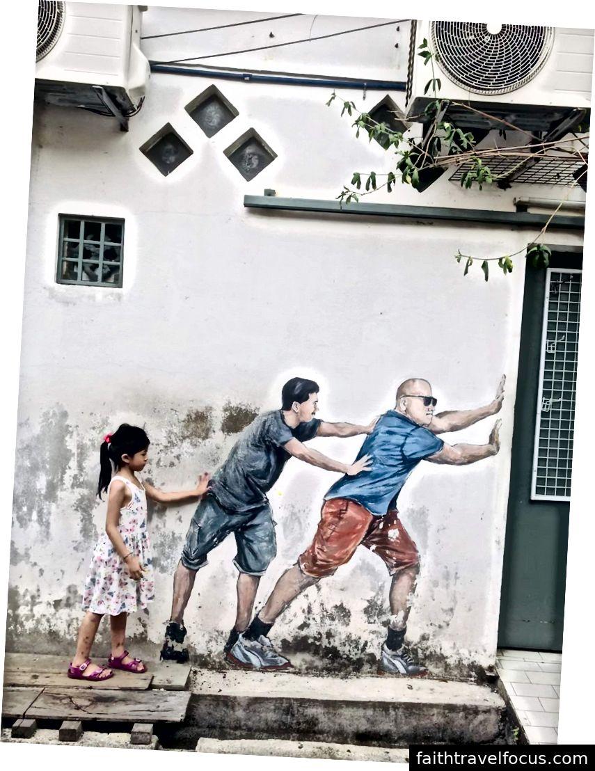En liten tjej som interagerar med en väggmålning