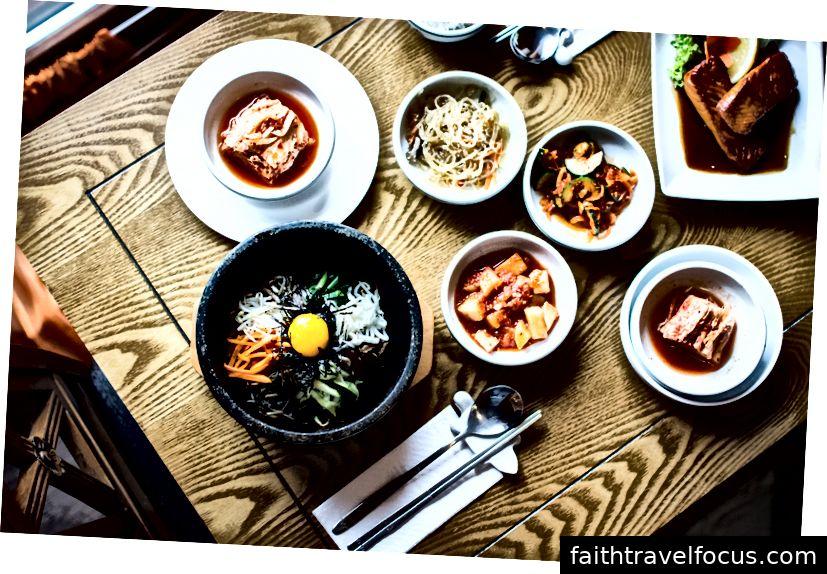 Zdjęcie Jakuba Kapusnaka na Unsplash - Kimchi na zdjęciu w lewym górnym naczyniu