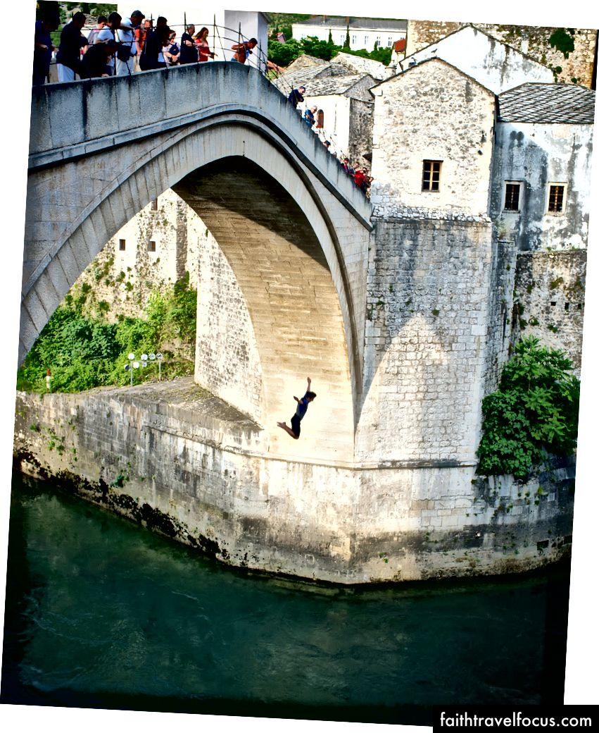 Подросток ныряет с восстановленного Стари Моста в разрушенном войной Мостаре, Босния. Бен Ху