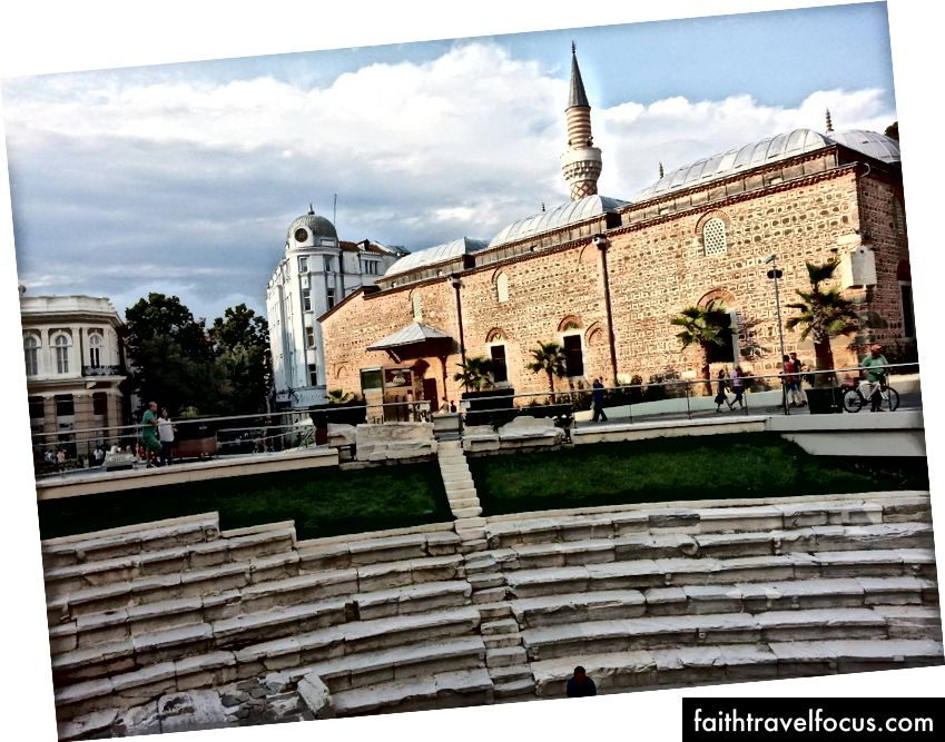 Древний римский Колизей, Османская мечеть (с пальмами) и колониальные европейские здания разделяют площадь Пловдива