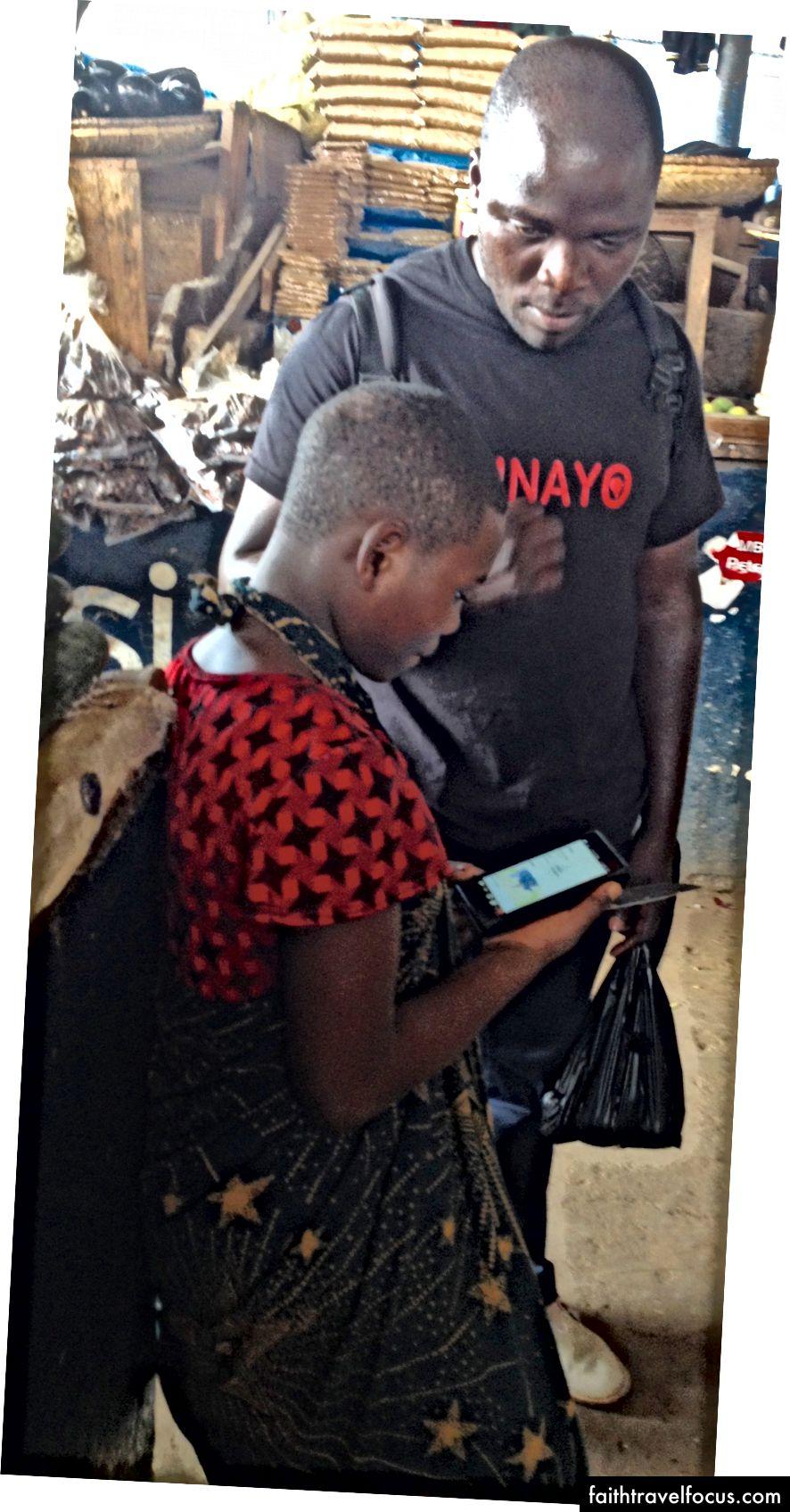 Član ekipe NINAYO Kassian Mwenda na prodajnem mestu NINAYO.com pokaže dekletu iz trgovine, kako najti boljše cene za svoje blago