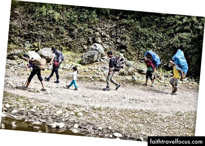 Trekking in de Khumbu-vallei, geflankeerd door dragers met ladingen tot 60kg. Porters verdienen tussen de $ 10 - $ 15 per dag met gekke ladingen.