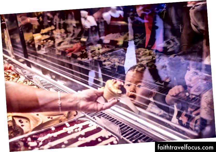 Một máy chủ cửa hàng gelato trêu chọc các Chows nhỏ. Với kem, bạn hầu như có thể khiến trẻ làm bất cứ điều gì. Venice, Ý.