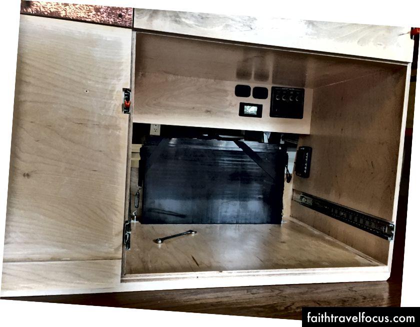 Pin được lắp đặt, công việc điện bắt đầu. Trên cùng bên phải là bảng chuyển đổi chính để tắt / tắt tủ lạnh, ổ cắm 12 v, ổ cắm 120v. Ngoài ra còn có một màn hình LCD trạng thái sạc cho thấy trạng thái của pin.