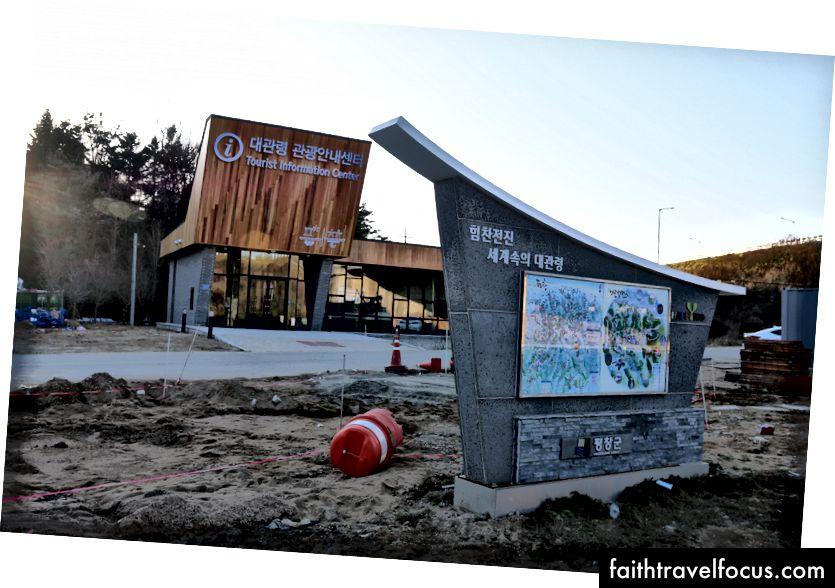 Trái: Dấu hiệu PyeongChang 2018 chào đón du khách đến thành phố Olympic. Phải: Trung tâm thông tin du lịch thành phố vẫn đang được xây dựng.