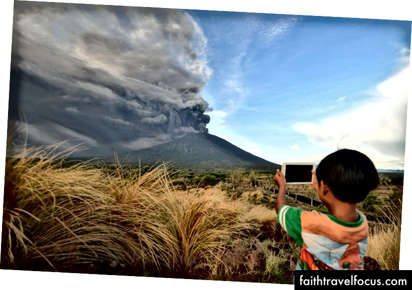 Хлопчик фотографується під час виверження гори Агунг, що спостерігається в районі Кубу в районі Карангасем на курортному острові Балі в Індонезії 26 листопада 2017 р. Фото Sonny Tumbelaka / AFP / Getty Images.