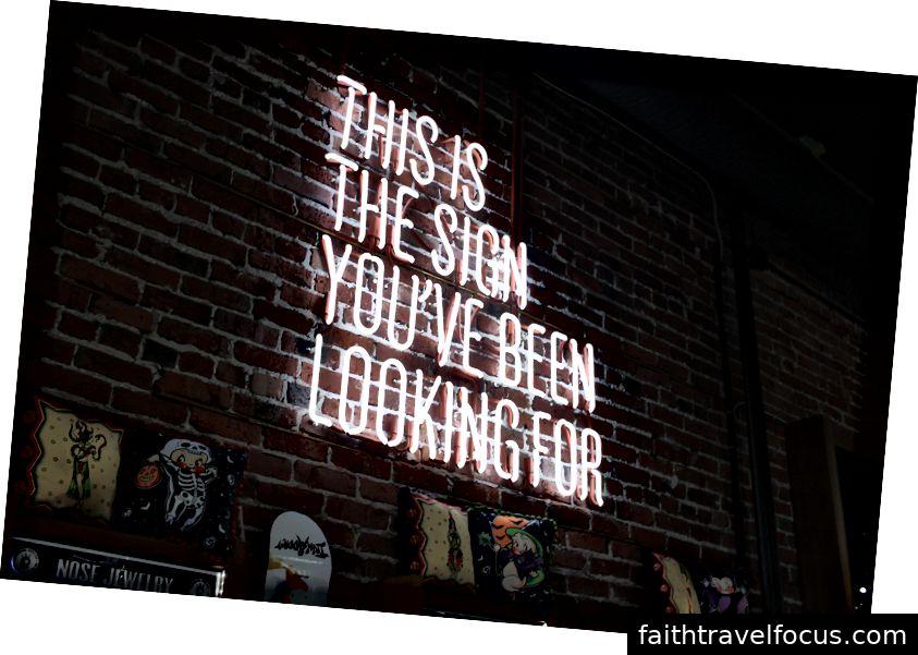 Một chiếc đèn neon sáng màu trên bức tường gạch trong một cửa hàng