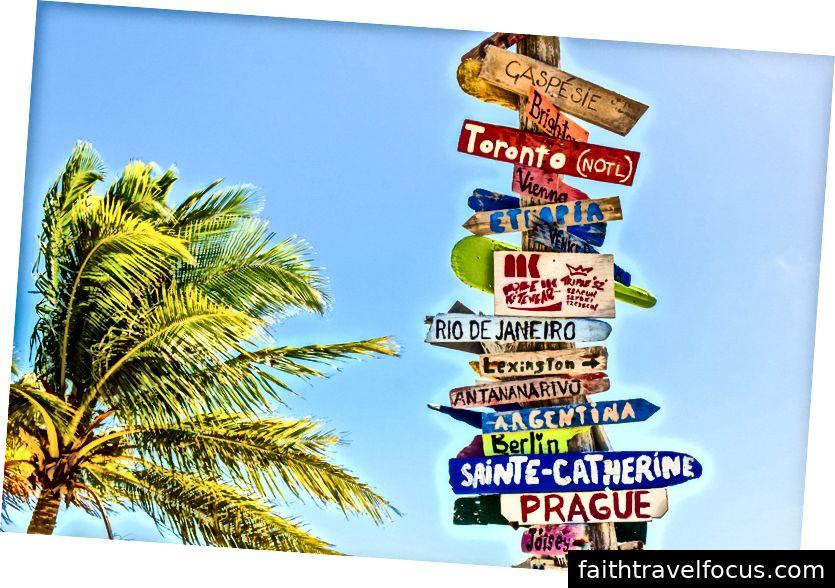 «Напрямні знаки на дерев'яному стовпі біля пальми на пляжі Лонг-Бей» від Діани Річі на Unsplash