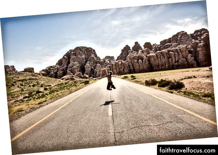 «Жінка в сонцезахисних окулярах підскакує посеред порожньої дороги зі скелястими відслоненнями на задньому плані» Жульєна Лавалье на Unsplash