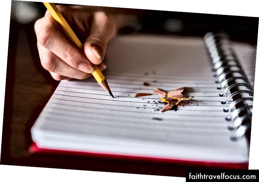 Một người viết bằng bút chì trong một cuốn sổ tay với những mảnh bút chì trên đó.