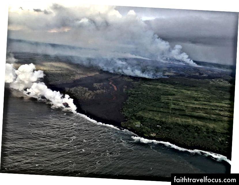 Sağ üstte gösterilen fissür kompleksi, kıvrımlı bir lav akışı beslemeye devam ediyor (ortada). En doğudaki lobda bulunan lav okyanusa giriyor (beyaz tüy). (USGS-HVO)