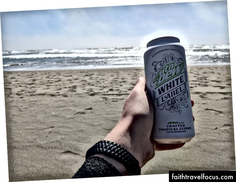 Пити білу етикетку роси Mtn на пляжі Тихого океану
