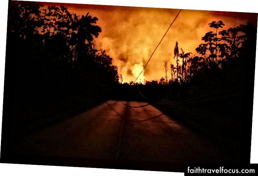 Dung nham từ khe nứt núi lửa Kīlauea chặn một con đường và chiếu sáng bầu trời đêm ở Leilani Estates, trên đảo Hawaii, Đảo lớn, vào ngày 25 tháng 5 năm 2018 tại Pāhoa, Hawaii. Các trận động đất nhỏ hơn và các đám tro lớn, cùng với sulfur dioxide phát ra, tiếp tục gây ra thảm họa cho đỉnh K summlauea và vùng rạn nứt phía đông thấp hơn. (Hình ảnh Mario Tama / Getty)