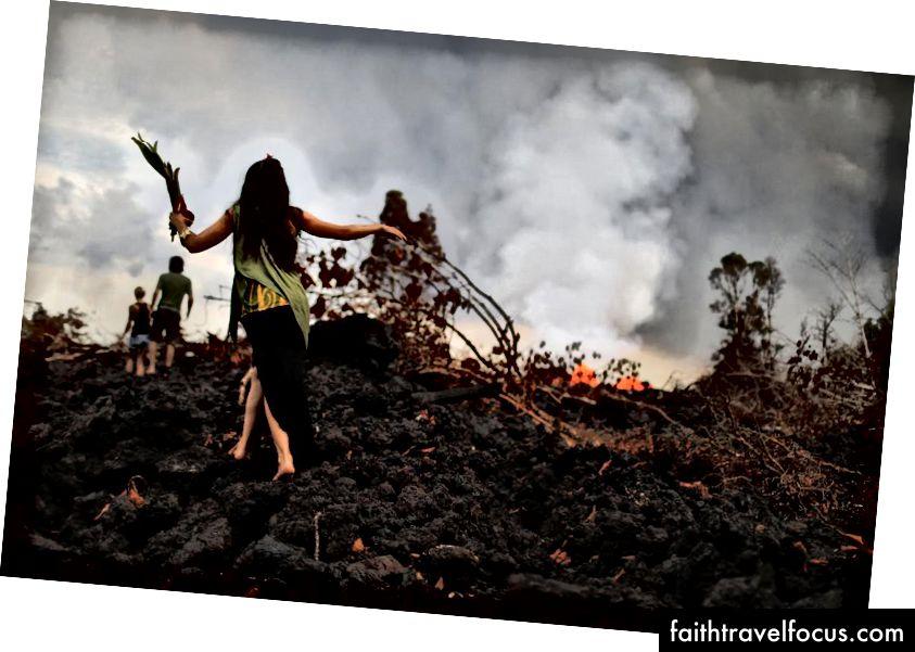 Một học viên hula truyền thống (L) mang theo một lời đề nghị trong khi đi bộ trên dòng dung nham mát lạnh gần đây từ khe nứt núi lửa Kīlauea, trên đảo Hawaii Hawaii, vào ngày 27 tháng 5 năm 2018 tại Pahoa, Hawaii. Lễ vật được để lại trong một buổi lễ cho Madame Pele, nữ thần núi lửa và lửa Hawaii. Hula là một hình thức nhảy của Hawaii kèm theo những bài hát hoặc bài hát theo dõi lịch sử và văn hóa của Hawaii. (Hình ảnh Mario Tama / Getty)
