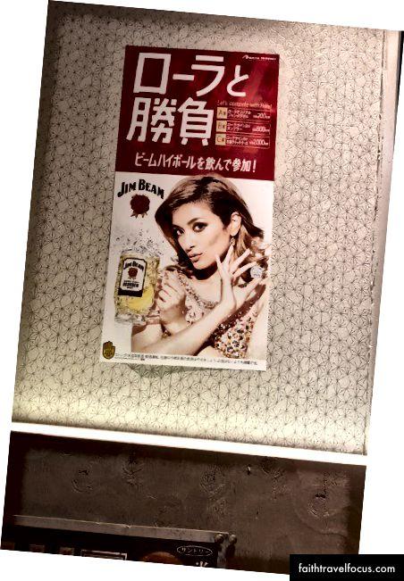 """""""Змагайся з Лолою! Випий Джім Бім Хайбол та приєднуйся! """"Плакат із зображенням японської моделі Лола, що рекламує призовий конкурс, зосереджений навколо Джима Біма Хайбола. Я надіслав дружині цю фотографію однієї ночі за допомогою тексту і запитав її:"""